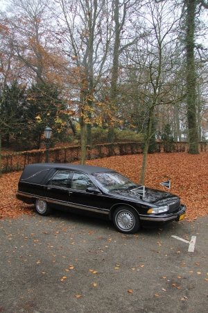 Black hearse near a cemetary in the autumn photo