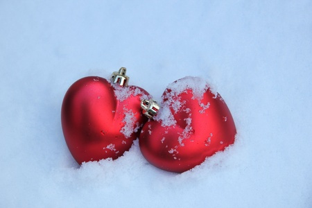 Two red, heart shaped christmas ornaments in fresh snow photo
