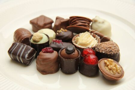Belgium chocolates, decorated with nuts and fruits photo