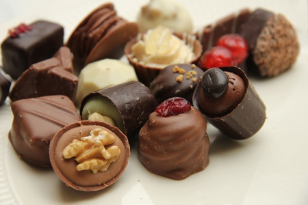Delicious chocolates from Belgium, decorated with nuts and fruits photo
