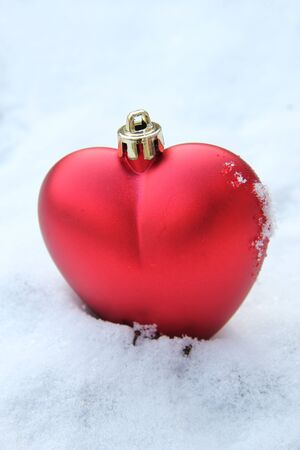 Red, heart shaped christmas ornament in fresh snow photo
