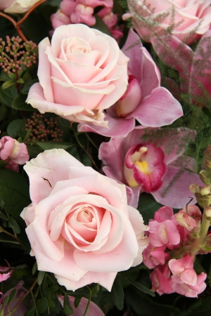 Soft pink rose and orchid in a bridal bouquet photo