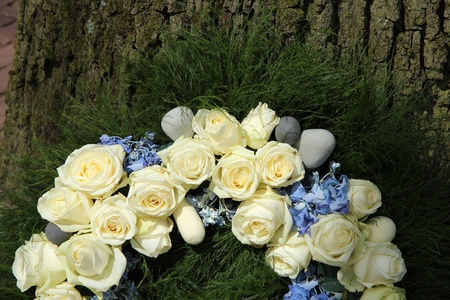 Detail of a sympathy wreath with white roses and blue hydranghea photo