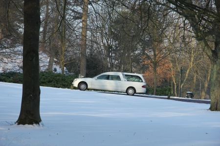 A white hearse at a snow covered cemetary