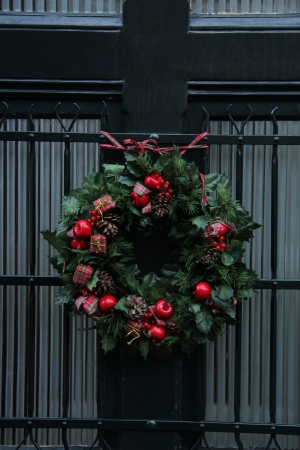 Christmas wreath with red apples and small giftes on a glass door photo