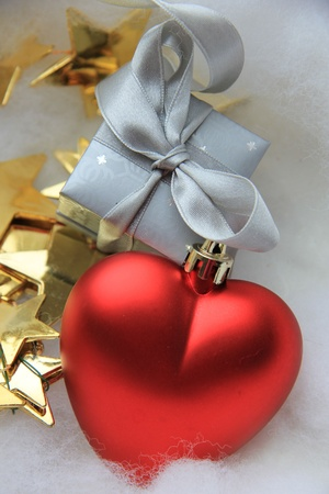 Silver christmas gift and golden decorations, red heart photo