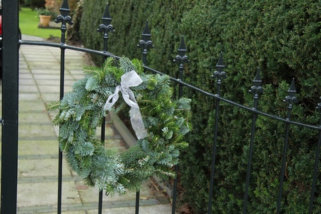Classic steel fence decorated with a traditional christmas wreath photo