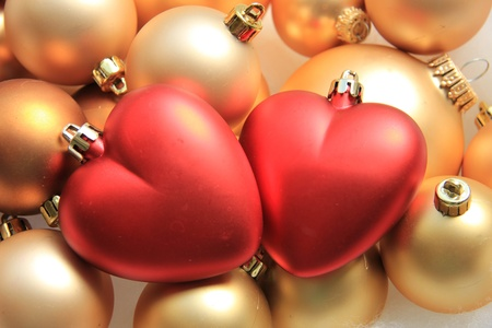 Red heart shaped christmas ornaments on a pile of golden ornaments Stock Photo - 19828638