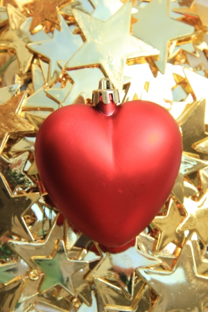 Big red heart shaped ornament on a pile of golden christmas ornaments photo