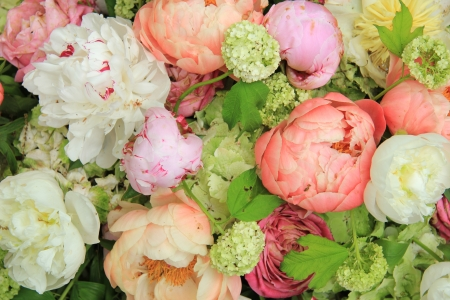 Peonies in various shades of pink and white in a floral wedding arrangement