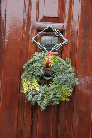 Plain green christmas wreath on a classic wooden door photo