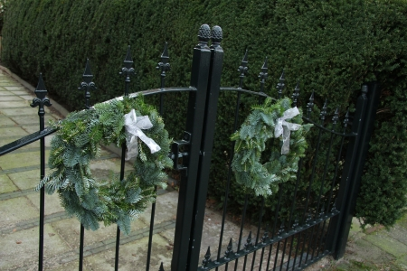 christmas wreaths: Classic steel fence decorated with a traditional christmas wreaths