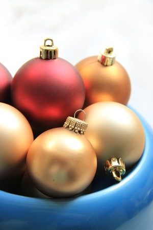 Red and golden christmas ornaments in a blue bowl photo
