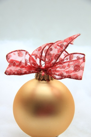 Golden christmas ornament with a lace bow photo