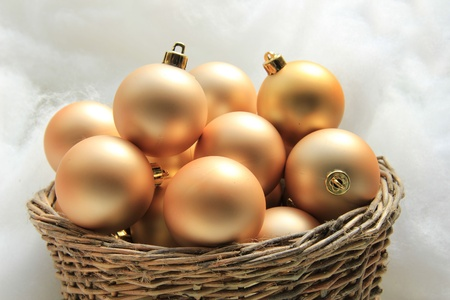 Golden christmas ornaments in a wicker basket photo