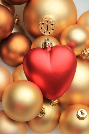 A red heart shaped ornament on a pile of golden christmas ornaments photo