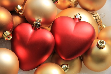 Red heart shaped christmas ornaments on a pile of golden ornaments photo