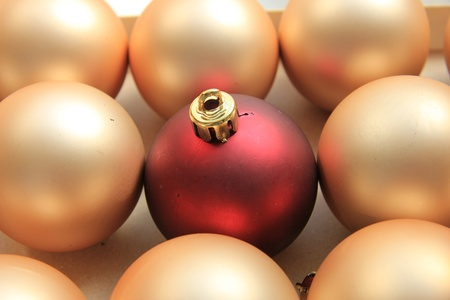 single red ornament on a pile of golden christmas ornaments photo