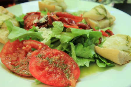 Goat cheese tomato salad with condiments, close up photo