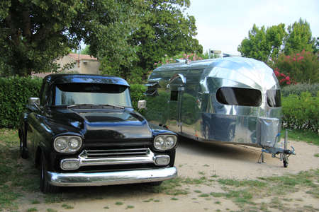 fourwheeldrive: Vintage car and caravan at a camping site Editorial