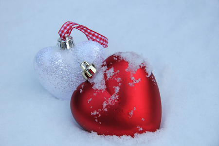 White and red heart shaped ornaments in fresh fallen snow photo