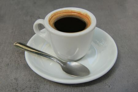 Fresh cup of espresso on a grey table photo
