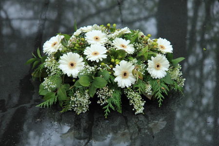 White funeral flowers on a grey marble tomb