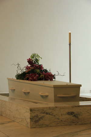 mortality: White coffin with funeral flowers in a crematorium