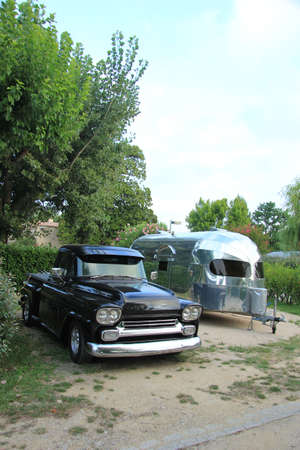 airstream: Vintage car and caravan at a camping site Stock Photo