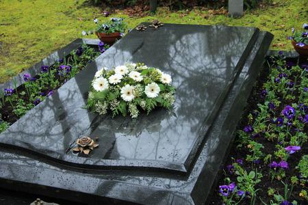 灰色の大理石の墓に白い葬儀の花