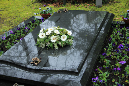 casket: White funeral flowers on a grey marble tomb
