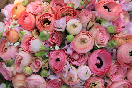 Pink roses and ranunculus in a bridal bouquet photo