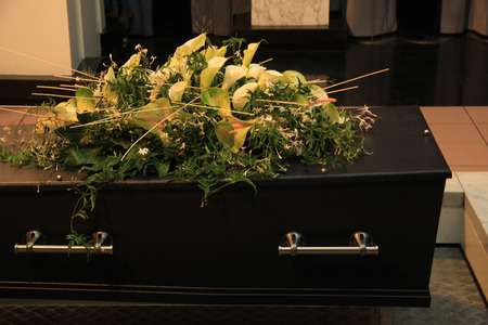 Wooden casket with funeral flowers, cremation ceremony photo