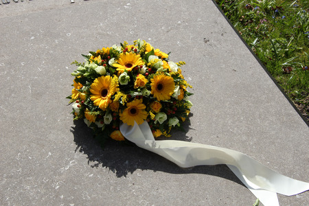 sympathy: yellow sympathy flowers on a tombstone