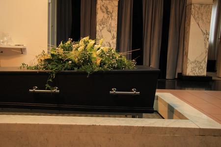 crematorium: Wooden casket with funeral flowers, cremation ceremony