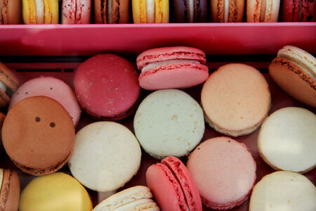 Macarons in different colors and flavors in a pink box photo