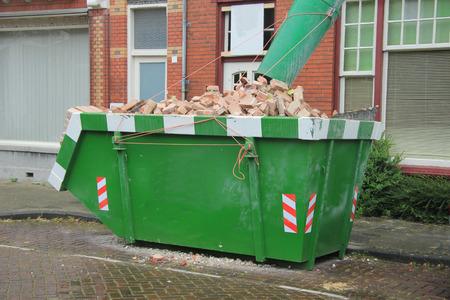 Geladen dumpster de buurt van een bouwplaats, huis renovatie Stockfoto