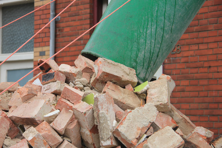 Old bricks and a waste chute near a dumpster