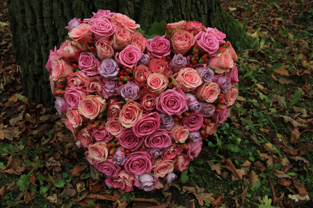 mourn: Heart shaped sympathy flower arrangement near a tree: different shades of pink roses