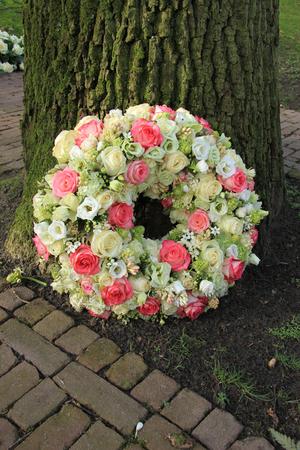 木、ピンクと白バラの近くの同情の花輪 写真素材
