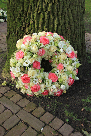 Sympathy wreath near a tree, pink and white roses