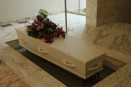 coffin: White coffin with funeral flowers in a crematorium