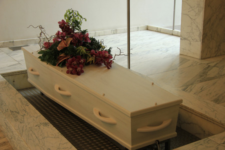 cremation: White coffin with funeral flowers in a crematorium