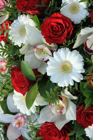 Bridal arrangement in red and white, cymbidium orchids, red roses and white gerberas photo