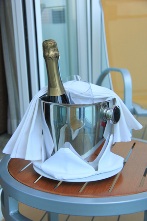 A bottle of champagne and glasses, waiting in a bucket to be served photo