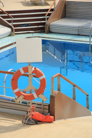 savety: Swimming pool area at a cruise ship with bar and lounge area Editorial