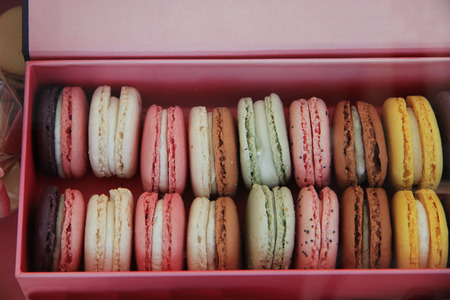 Macarons in different colors and flavours in a pink box photo