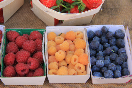 Raspberries and blueberries, displayed in boxes at a market photo