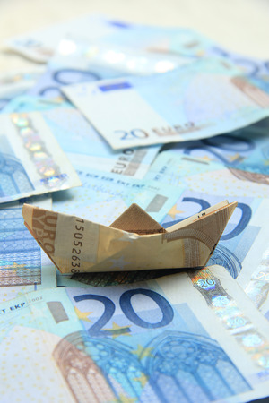 fifty euro banknote: A Fifty euro banknote boat on a twenty euro notes sea Stock Photo