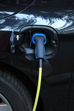 recharge: Hybrid car on recharge near an electric recharge station